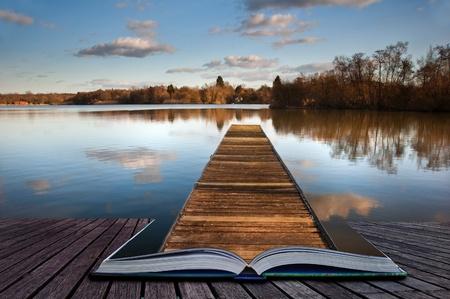Mooi beeld van zonsondergang landschap van houten vissen steiger op kalm meer met duidelijke reflecties coming out van pagina's in magische boek