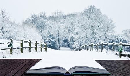 Sneeuw Winterlandschap platteland scène met Engels platteland die uit pagina's in magische boek Stockfoto