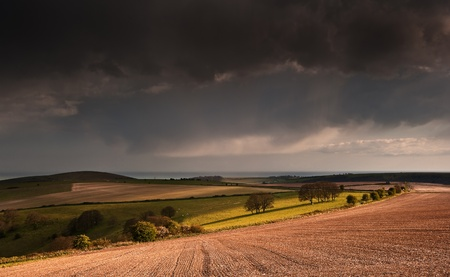 Beautiful landscape over agricultural fields with moody sky and invigorating sunlight photo
