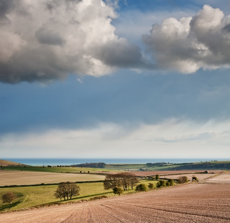 english countryside: Beautiful landscape over agricultural fields with moody sky and invigorating sunlight