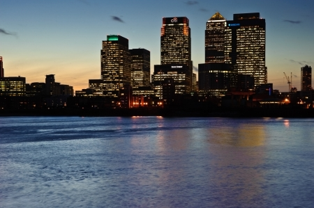 View of London City skyline at night on clear sky with reflections in River Thames