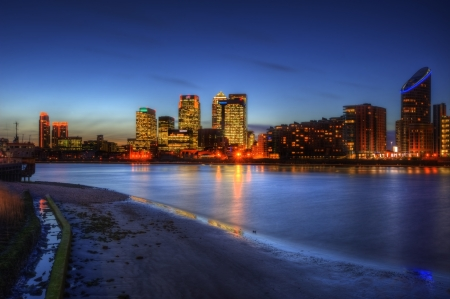 east end: View of London City skyline at night on clear sky with reflections in River Thames Editorial