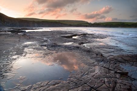 Beautiful sunrise landscape image at Kimmeridge Bay on Jurassic Coast, Dorset, England photo