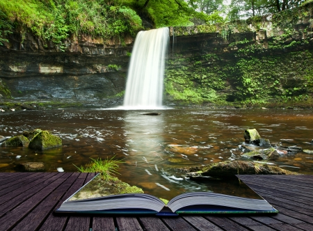 Creatieve samengesteld beeld van waterval in de bossen in de pagina's van magische boek