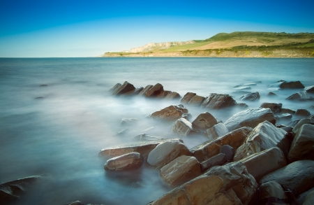 Seascape with Kimmeridgian rock ledges extending out to sea on blue sky day