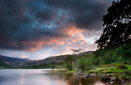 Stunning colorful sunrise over Llyn Gwynant in Snowdonia National Park with Carneddau mountain range in distance Stock Photo - 15661176
