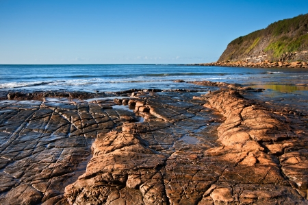 kimmeridge bay: Seascape with Kimmeridgian rock ledges extending out to sea on blue sky day