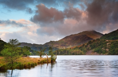 View of sunrise over Llyn Gwynant towards landscape of Yr Afan mountain in Snowdonia National Park photo
