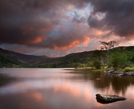 Stunning colorful sunrise over Llyn Gwynant in Snowdonia National Park with Carneddau mountain range in distance photo