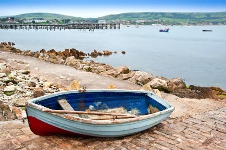 古い海辺の町のスリップウェイでのボートこぎ