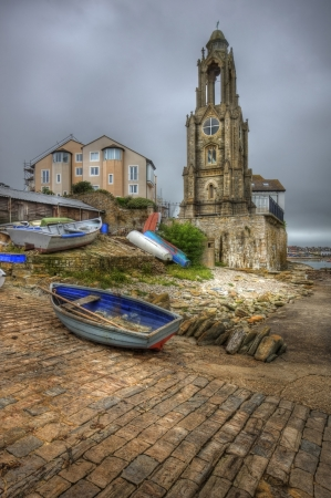 quaint: Old seaside town with lookout tower on seashore and rowing boat in foreground