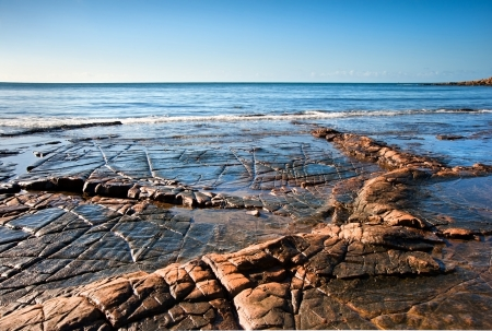 Seascape with Kimmeridgian rock ledges extending out to sea on blue sky day photo
