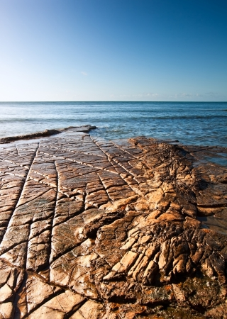 Seascape with Kimmeridgian rock ledges extending out to sea on blue sky day Stock Photo - 16217377
