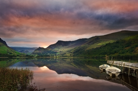 View of Snowdon covered in cloud at sunrise from Llyn Nantlle with reflections in lake and vibrant colors with rowing boats moored at jetty photo