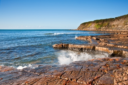 Seascape with Kimmeridgian rock ledges extending out to sea on blue sky day Stock Photo - 16440517