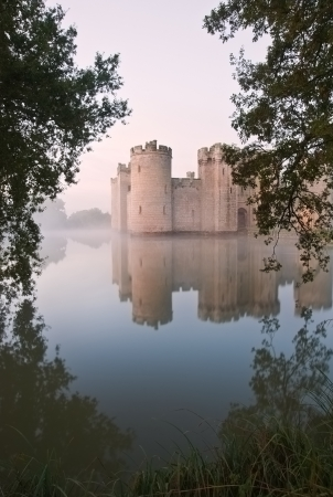 Beautiful medieval castle and moat at sunrise with mist over moat and sunlight behind castle Stock Photo - 16870625