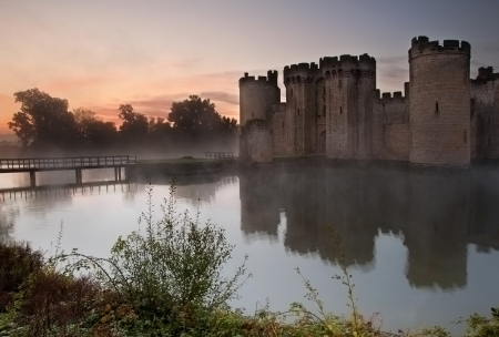 Beautiful medieval castle and moat at sunrise with mist over moat and sunlight behind castle Stock Photo - 16870624