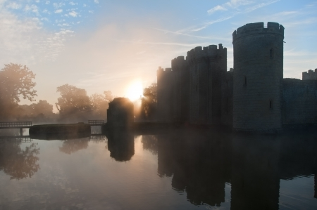 Beautiful medieval castle and moat at sunrise with mist over moat and sunlight behind castle Stock Photo - 16870623