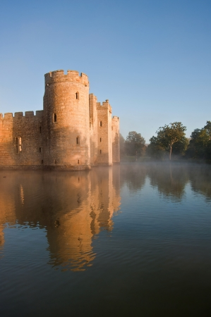 Beautiful medieval castle and moat at sunrise with mist over moat and sunlight behind castle Stock Photo - 16870622