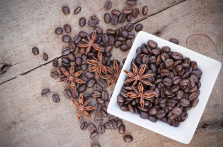 Star anise and coffee beans in white ceramic bowl on wooden background photo