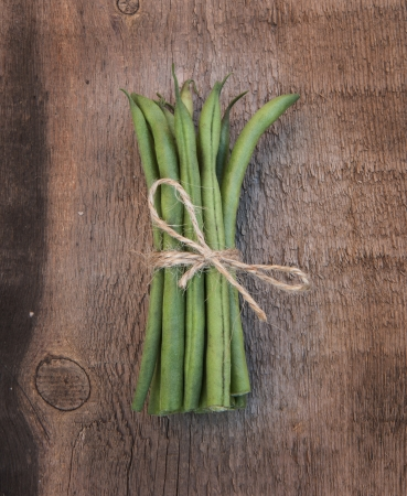 Fresh French green beans on grunge worn wooden background photo