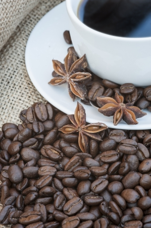Coffee cup and saucer on hessian cloth surrounded by coffee beans photo