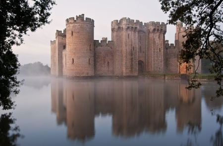 Beautiful medieval castle and moat at sunrise with mist over moat and sunlight behind castle Stock Photo - 17069368