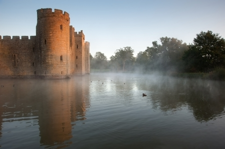 Beautiful medieval castle and moat at sunrise with mist over moat and sunlight behind castle Stock Photo - 17069365