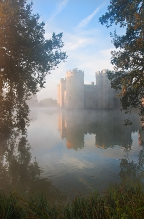 Beautiful medieval castle and moat at sunrise with mist over moat and sunlight behind castle Stock Photo - 17069370