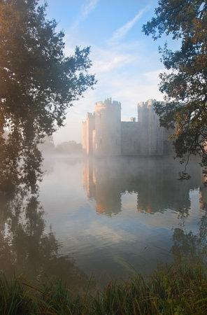 castillo medieval: Hermoso castillo medieval y el muro al amanecer con niebla sobre foso y la luz del sol detrás de castillo Editorial