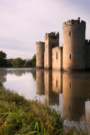 Beautiful medieval castle and moat at sunrise with mist over moat and sunlight behind castle Stock Photo - 17069372