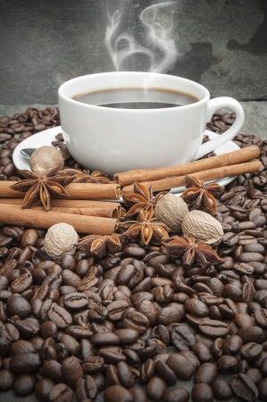 Steaming hot Coffee cup with anise, cinnamon, nutmeg and coffee beans photo