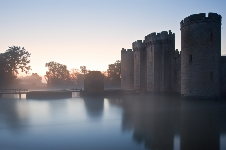 slits: Beautiful medieval castle and moat at sunrise with mist over moat and sunlight behind castle