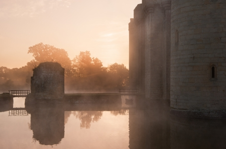 Beautiful medieval castle and moat at sunrise with mist over moat and sunlight behind castle Stock Photo - 17146907