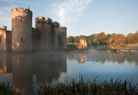Beautiful medieval castle and moat at sunrise with mist over moat and sunlight behind castle Stock Photo - 17146909