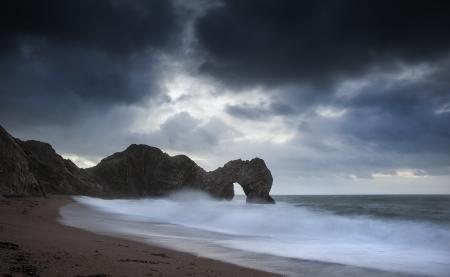 durdle door: Stormy pre-dawn over Durdle Door on Jurassic Coast England Stock Photo