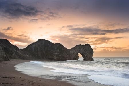 Sunrise behind Durdle Door on Jurassic Coast in England photo