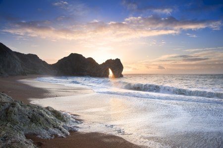 durdle: Beautiful sunrise over ocean with rock stack in foreground Stock Photo