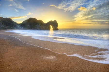 Beautiful sunrise over ocean with rock stack in foreground photo