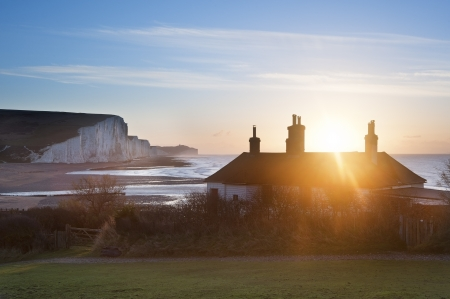 coastguard: Sun bursts over coastguard cottages at Seaford Head with Seven Sisters cliffs in background