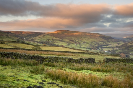 sulight: Swaledale in Yorkshire Dales National Park at sunrise with sun lighting hills Stock Photo