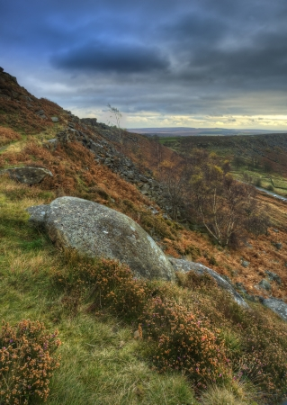 Abandoned millstones on Curbar Edge in Peak District National Park with Froggatts Edge in background photo