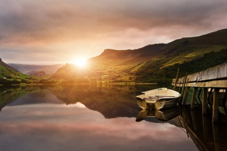 Sunrise over lake with boats moored at jetty photo