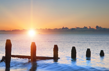 groynes: Old groynes decaying on beach against incoming tide at sunrise