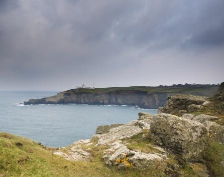 headland: Stormy sky over headland peninsula with lighthouse Stock Photo