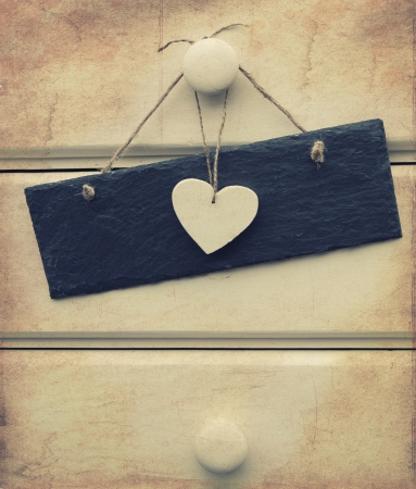 Macro retro cross processed effect image of heart and slate sign on wooden background photo