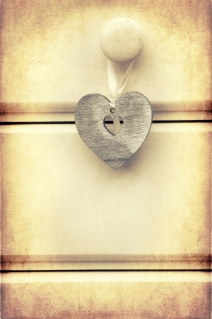 Macro retro cross processed effect image of wood heart on wooden background photo