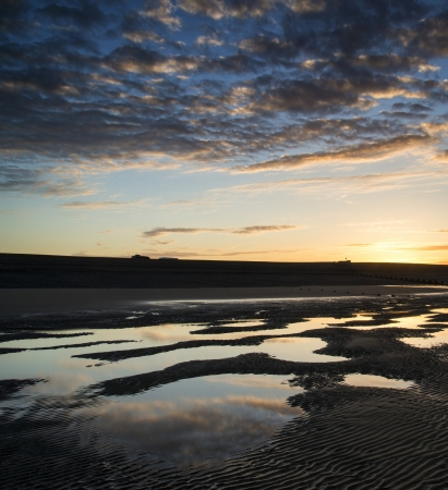 Beautiful sunrise reflected in low tide water pools on beach landscape photo