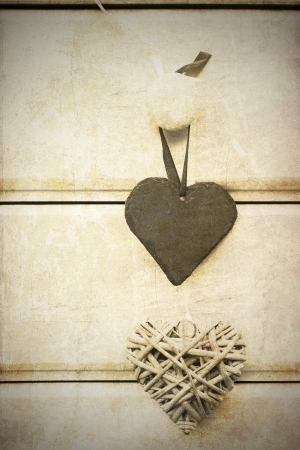 Macro retro cross processed effect image of slate and willow hearts on wooden background photo
