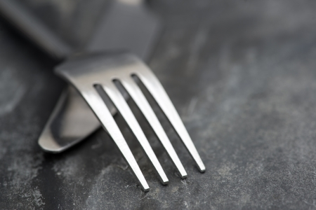 現代ナイフとフォークを素朴なスレートの背景上のマクロ画像